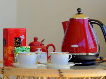 a red electric kettle, tea pot, tea caddy, white cups and a sugar bowl