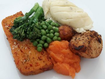 plate of food with a vegetable loaf, broccoli, peas, mashed carrot, roast and mashed potato